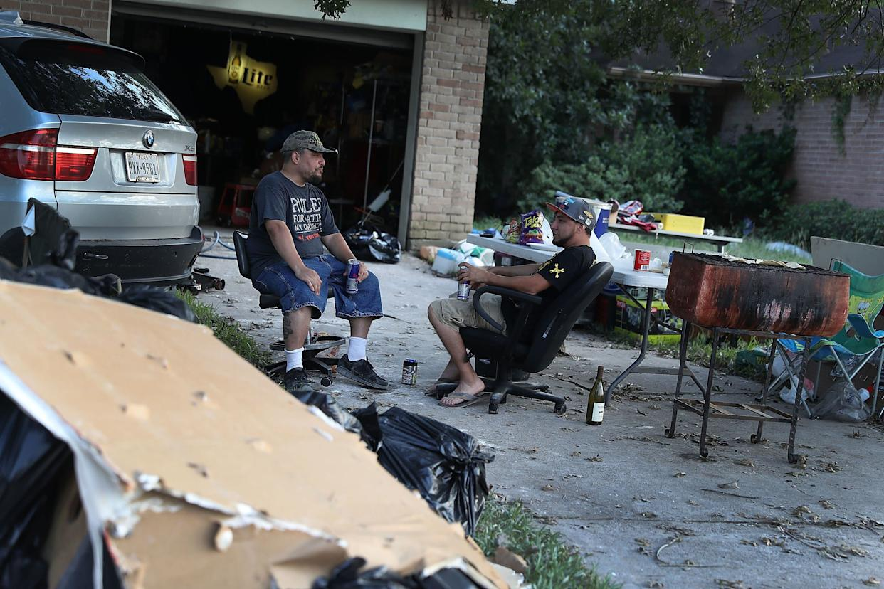 Artemio Tamez and Franco Tamez sit in front of Franco's house on Sept. 2 after spending the day cleaning it outafter torrential rains in the wake of Hurricane Harvey caused widespread flooding throughout the Houston area.