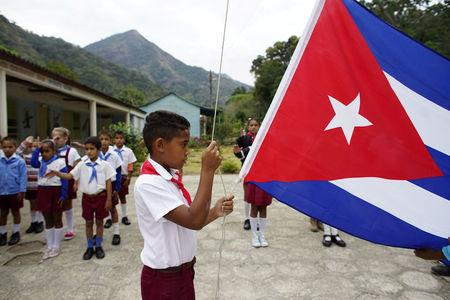A boy raises the Cuban flag during a daily ceremony held at a school in the village of Santo Domingo, in the Sierra Maestra, Cuba, April 2, 2018. REUTERS/Alexandre Meneghini