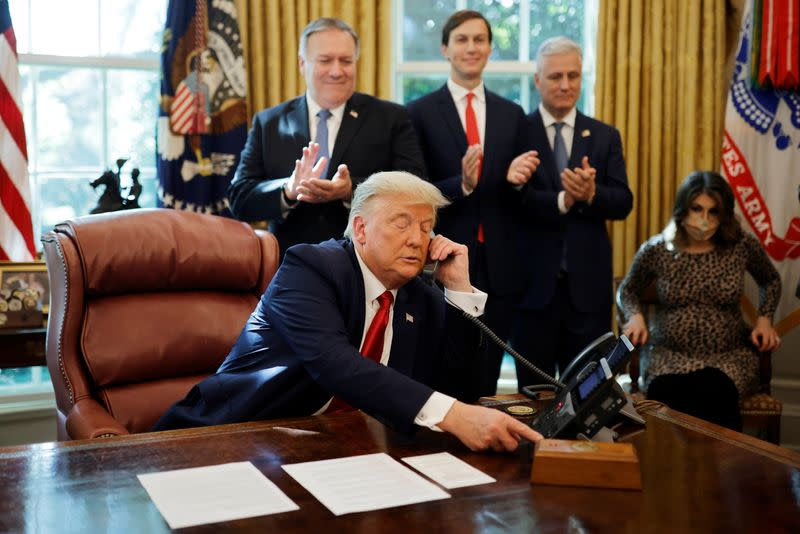U.S. President Donald Trump is seen on the phone with leaders of Israel and Sudan in the Oval Office at the White House in Washington
