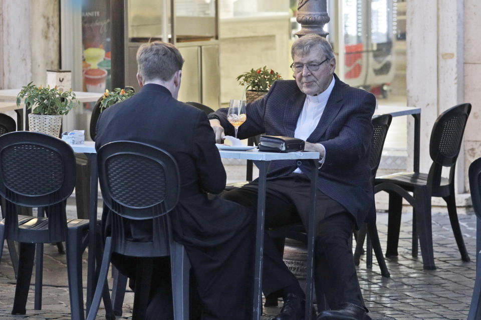 Cardinal George Pell, right, has a drink in a cafe at the Vatican, Sunday, Oct. 4, 2020. Cardinal George Pell, who left the Vatican in 2017 to face child sexual abuse charges in Australia, returned to Rome on Wednesday to find a Holy See mired in the type of corruption scandal he worked to expose and clean up. (AP Photo/Gregorio Borgia)