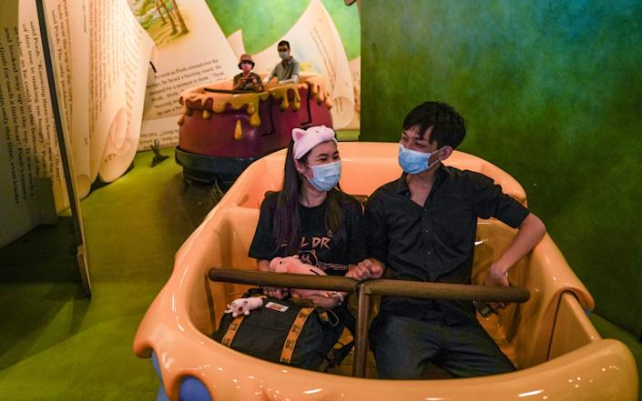 Visitors wear protective masks while riding the Many Adventures of Winnie the Pooh ride at Disneyland in Hong Kong, which reopened today - Bloomberg