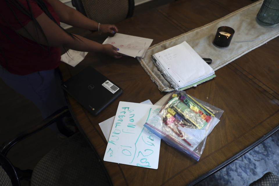 Brittany Preston, a mother of six, cleans the leftover school supplies from the dining room table upon finishing virtual classes, Wednesday, Feb. 10, 2021, in Chicago. (AP Photo/Shafkat Anowar)