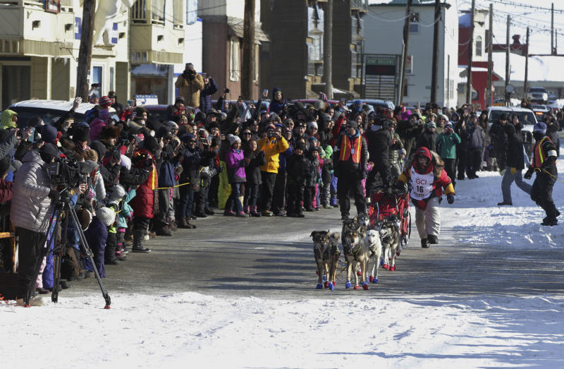 Mitch Seavey, of Sterling, Alaska, runs towards the finish line under the Burled Arch, winning the 1,000-mile Iditarod Trail Sled Dog Race, in Nome, Alaska, Tuesday, March 14, 2017. Seavey won his third Iditarod Trail Sled Dog Race on Tuesday, becoming the fastest and oldest champion at age 57 and helping cement his family's position as mushing royalty. (AP Photo/Diana Haecker)