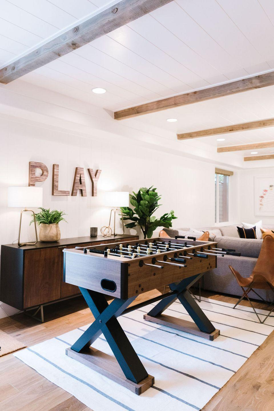 """<p>This family-friendly basement living room is filled with fun touches, like an oversized Ferris wheel print, a """"PLAY"""" wall sign, and the most beautiful modern foosball table you'll ever see. Let the games begin!</p><p><strong>See more at <a href=""""https://stagg-design.com/all/basement-kitchen-reveal-project-modern-family/"""" rel=""""nofollow noopener"""" target=""""_blank"""" data-ylk=""""slk:Stagg Design"""" class=""""link rapid-noclick-resp"""">Stagg Design</a>. </strong></p><p><a class=""""link rapid-noclick-resp"""" href=""""https://go.redirectingat.com?id=74968X1596630&url=https%3A%2F%2Fwww.walmart.com%2Fip%2FBest-Choice-Products-48in-Competition-Sized-Soccer-Foosball-Table-w-2-Balls-2-Cup-Holders-for-Home-Game-Room-Arcade%2F51883102&sref=https%3A%2F%2Fwww.redbookmag.com%2Fhome%2Fg36061437%2Fbasement-ideas%2F"""" rel=""""nofollow noopener"""" target=""""_blank"""" data-ylk=""""slk:SHOP FOOSBALL TABLES"""">SHOP FOOSBALL TABLES</a></p>"""