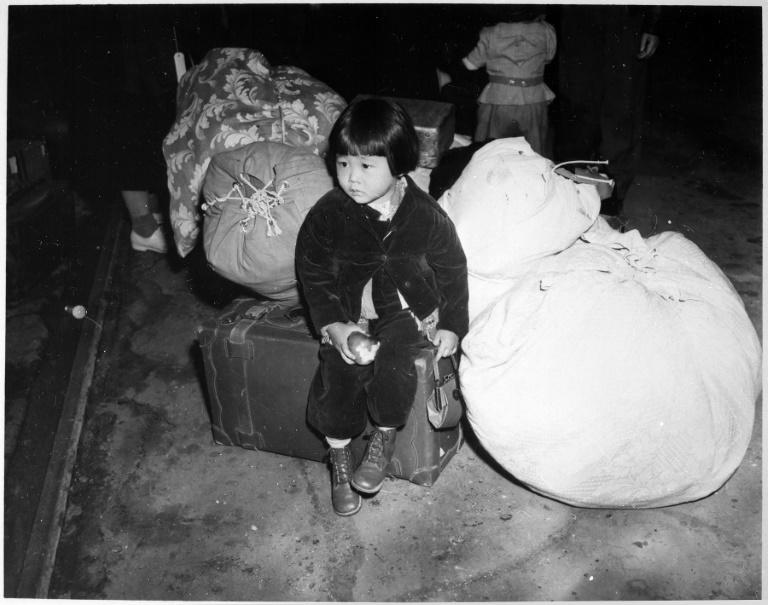 This photo obtained July 21, 2020 courtesy of the US National Archives shows two-year-old Yuki Okinaga Hayakawa, an  evacuee of Japanese ancestry waiting with the family baggage before leaving by bus for an assembly center in the spring of 1942, taken by War Relocation Authority (WRA) photographer by Clem Albers, in Los Angeles,California, April 1942.Yuki Okinaga Hayakawa Llewellyn, an American of Japanese descent in a 1942 photograph that moved Americans, died almost eight decades after being sent with her mother, Mikiko Hayakawa, to the Manzanar War Relocation Center. Little Yuki, photographed sitting on a suitcase at Union Station in Los Angeles, has become a symbol of one of the least glorious pages in US history.  She died on March 8, 2020, at the age of 81, a death that went unnoticed in the midst of a coronavirus pandemic until one of her relatives recently contacted the Los Angeles Times