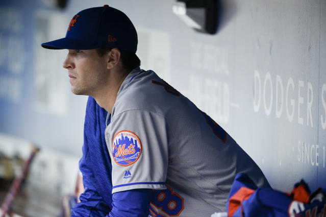 FILE - In this Sept. 3, 2018, file photo, New York Mets' Jacob deGrom watches from the dugout prior to the team's baseball game against the Los Angeles Dodgers in Los Angeles. NL Cy Young winner deGrom wants to hear the Mets best pitch on a multiyear contract by opening day--and the team thinks thats a good call, too. New general manager Brodie Van Wagenen, who was deGroms agent before switching sides at the bargaining table last fall, told reporters Tuesday, Feb. 12, at spring training theres no reason for a distraction to carry into the regular season. (AP Photo/Kelvin Kuo, File)