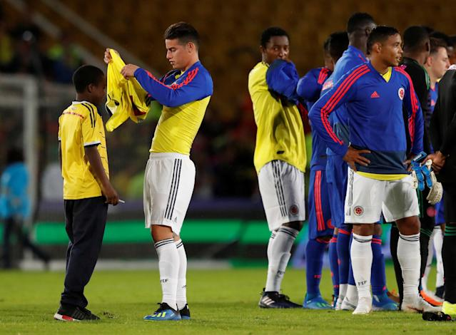 Soccer Football - Farewell Soccer Match - Colombia national team - Nemesio Camacho El Campin, Bogota, Colombia May 25, 2018. Colombia's player James Rodriguez puts a t-shirt on a child after the end of a farewell ahead of the upcoming FIFA World Cup Russia 2018. REUTERS/Henry Romero
