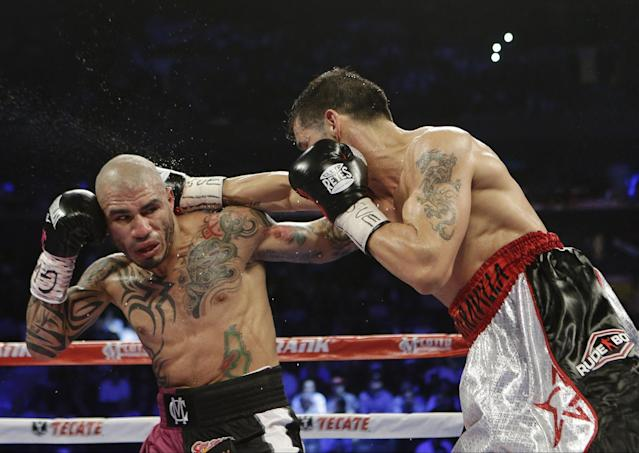 Miguel Cotto and Sergio Martinez trade blows during their fight Saturday. (AP)
