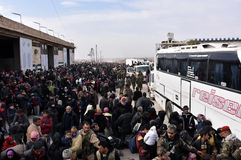 Syrian families, fleeing from various eastern districts of Aleppo, queue to get onto buses on November 29, 2016 (AFP Photo/George Ourfalian)
