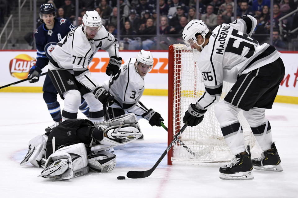 Los Angeles Kings' Kurtis MacDermid (56) helps goaltender Jonathan Quick (32) defend against the Winnipeg Jets during second period NHL action in Winnipeg on Tuesday, Oct. 22, 2019. THE CANADIAN PRESS/Fred Greenslade/The Canadian Press via AP)
