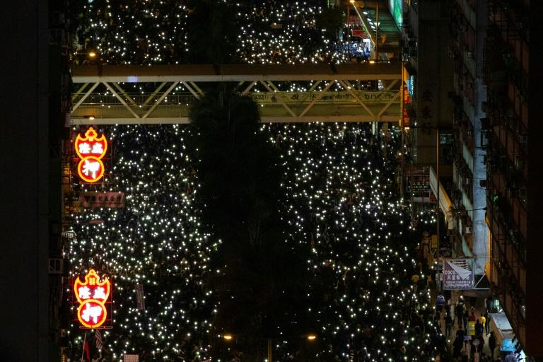 As night fell the crowds switched on their mobile phone torches, creating a glittering carpet of lights that stretched far into the distance, their chants bouncing off the towering skyscrapers above (AFP Photo/Alastair Pike)