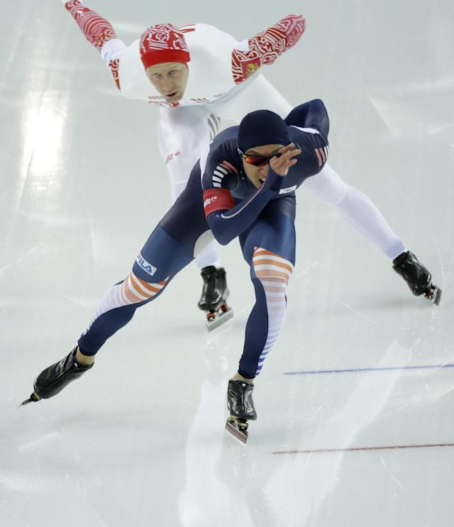 South Korea's Lee Kyou-hyuk, front, and Russia's Igor Bogolyubsky compete in the men's 1,000-meter speedskating race at the Adler Arena Skating Center at the 2014 Winter Olympics, Wednesday, Feb. 12, 2014, in Sochi, Russia. (AP Photo/David J. Phillip )