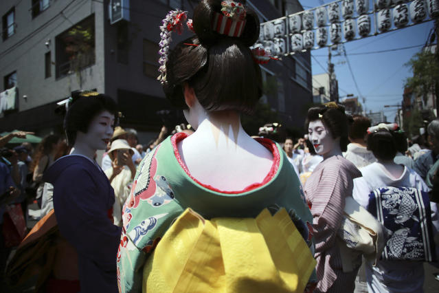 <p>Geisha girls prepare to parade down the streets toward Asakusa Shrine in the compound of Sensoji Temple, May 19, 2017, in Tokyo prior to the annual Sanja Festival, one of the city's three major festivals. (Photo: Eugene Hoshiko/AP) </p>