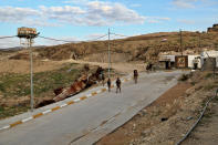 Iraqi army soldiers walk down the road leading to the Sayida Zeinab shrine in Sinjar, Iraq. Friday Dec. 4, 2020. A new agreement aims to bring order to Iraq's northern region of Sinjar, home to the Yazidi religious minority brutalized by the Islamic State group. Since IS's fall, a tangled web of militia forces have run the area, near the Syrian border. Now their flags are coming down, and the Iraqi military has deployed in Sinjar for the first time in nearly 20 years. (AP Photo/ Samya Kullab)