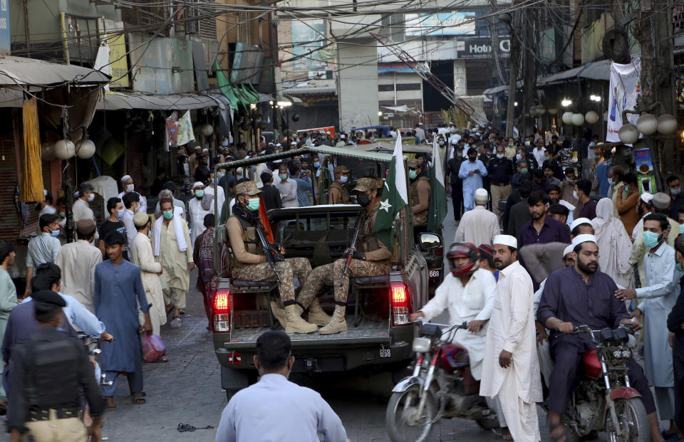 Pakistan army troops arrive to ensure new timing of market closing announced by government to control the spread of the coronavirus, in Peshawar, Pakistan, Saturday, April 24, 2021. (AP Photo/Muhammad Sajjad)