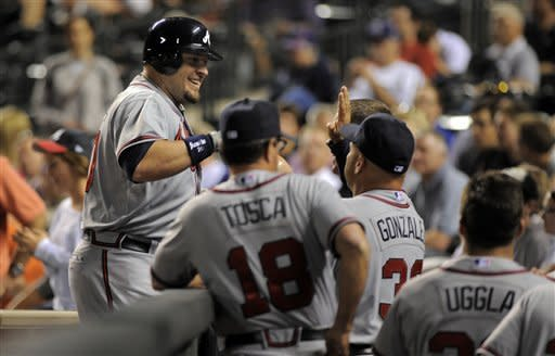 Atlanta Braves' Eric Hinske celebrates a two run home run off Colorado Rockies relief pitcher Edgmer Escalona with teammates during the 11th inning of a baseball game Friday, May 4, 2012, in Denver. (AP Photo/Jack Dempsey)