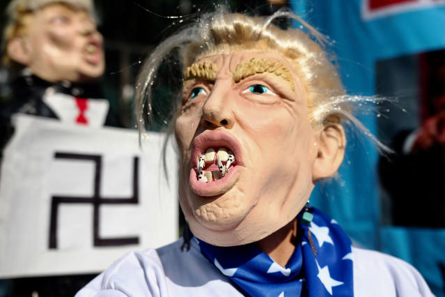 <p>An activist representing U.S President Donald Trump put fangs into a mask representing KKK members during a protest as part of the International Workers Day at the U.S embassy on May 01, 2017 in Mexico City. (Photo: Emilio Espejel/LatinContent/Getty Images) </p>