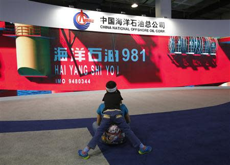 A boy looks at a promotional video about Chinese oil rig Haiyang Shi You 981 at a booth of China's state-run oil company CNOOC during China Beijing International High-Tech Expo in Beijing, May 16, 2014. REUTERS/Kim Kyung-Hoon