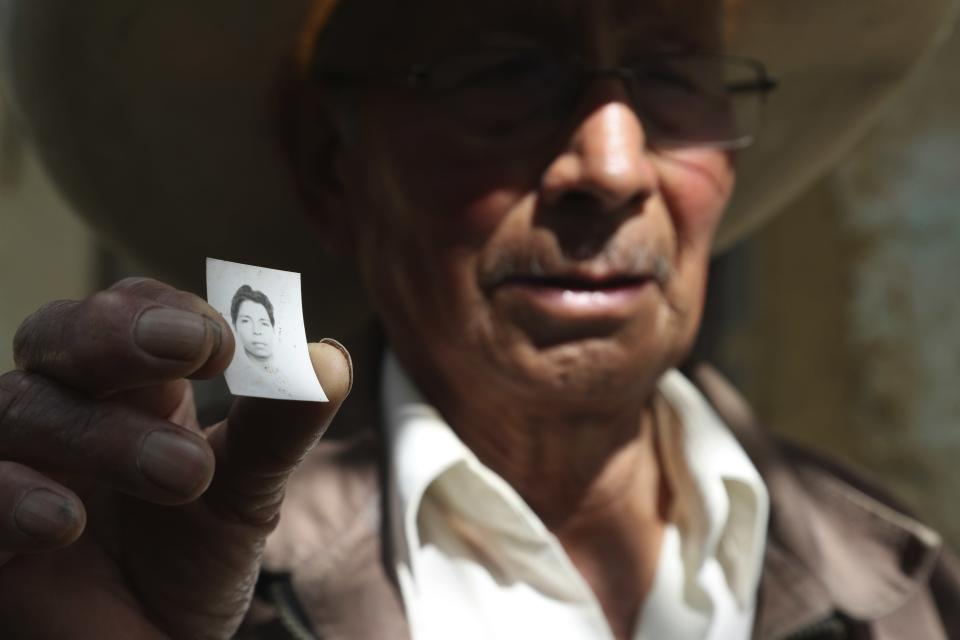 Ireño Castillo, the father of Free Peru party presidential candidate Pedro Castillo, shows an old photo of his son in Puna, Peru, Friday, April 16, 2021. Castillo's son, who has proposed rewriting Peru's constitution and deporting all immigrants living in the country illegally who commit crimes, will face rival candidate Keiko Fujimori in the June 6 presidential run-off election. (AP Photo/Martin Mejia)