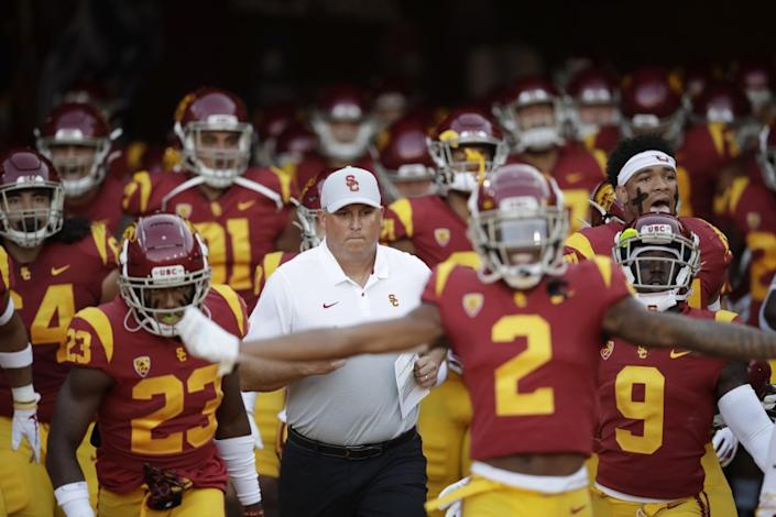 Southern California coach Clay Helton, center, runs onto the field with his team for an NCAA college football game against Utah on Friday, Sept. 20, 2019, in Los Angeles. (AP Photo/Marcio Jose Sanchez)