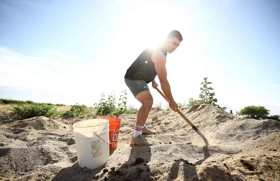 TULARE, CALIFORNIA - JUNE 06:  Olympic hopeful boxer Richard Torrez Jr.  shovels sand into buckets during a training session on June 06, 2020 in Tulare, California. Torrez Jr. was one of 13 boxers selected to represent Team USA at the Tokyo 2020 Olympic Games Boxing Qualifiers in Argentina, but the qualifier was canceled due to the coronavirus. The 20-year-old has won numerous international tournaments, and is currently ranked fifth in the world in the super heavyweight weight class. The training center in Colorado is currently closed so Torrez Jr. continues to train at home with his father, who is his coach. His father has implemented many different types of training methods, such as hitting cement rocks with a sledge hammer, filling up wheel barrels with sand, and flipping over tractor tires. Athletes across the globe are now training in isolation under strict policies in place due to the Covid-19 pandemic.  (Photo by Ezra Shaw/Getty Images)