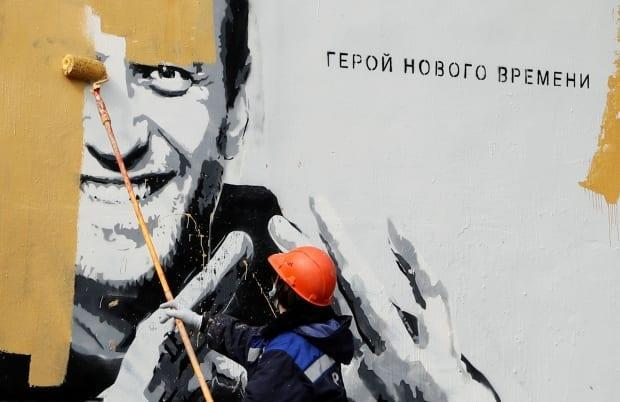 A worker paints over a picture of Navalny on a wall in Saint Petersburg, Russia, last month. The message reads: 'The hero of the new age.' Navalny, who is currently in prison, has been a thorn in the side of Russian President Vladimir Putin.
