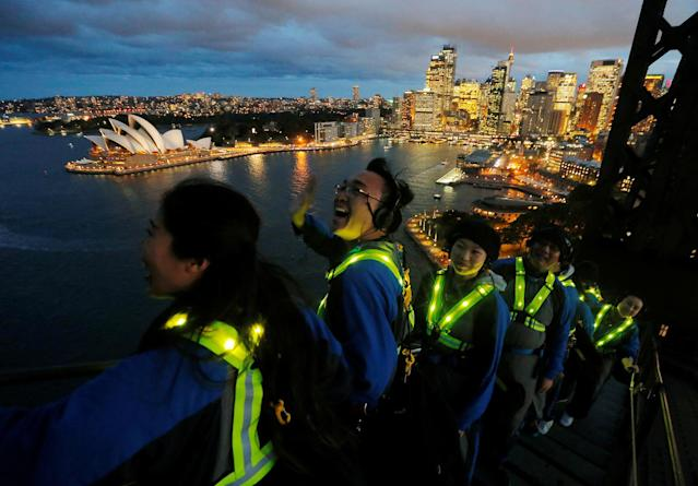 <p>Participants wear glowing vests as they look out to the Sydney Opera House from the Sydney Harbour Bridge in Australia May 18, 2018 during a press preview of the Vivid Climb Mandarin for Chinese-language tours of the Sydney icon. Sydney's Vivid festival of light and sound will begin May 26 with many of Sydney's landmarks participating in the annual event. (Photo: Jason Reed/Reuters) </p>