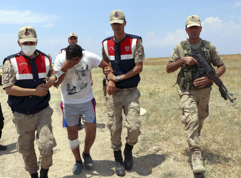 Paramilitary police detain a man in Lake Van, in eastern Turkey, Wednesday, July 1, 2020. Up to 60 migrants may have been trapped in a boat that sank in the lake last week, Turkey's Interior Minister Suleyman Soylu said Wednesday. Turkey launched a search-and-rescue mission involving helicopters and boats after the boat carrying migrants across Lake Van was reported missing on June 27. (DHA via AP)