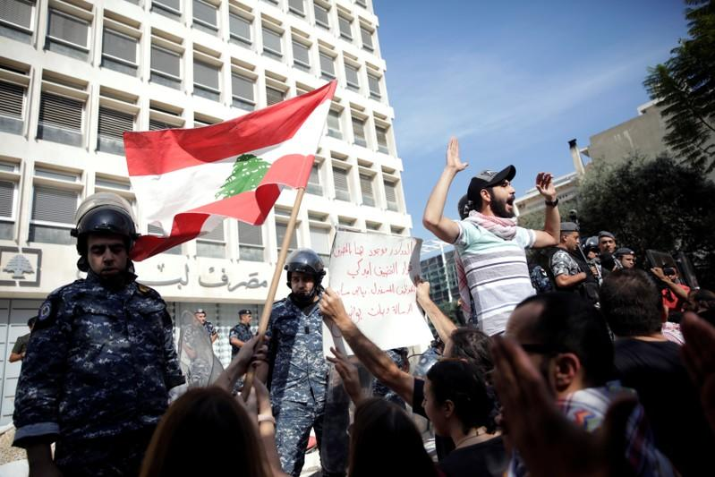 Police officers stand guard after protesters knocked down the fencing as they demonstrate outside of Lebanon Central Bank during ongoing anti-government protests in Beirut
