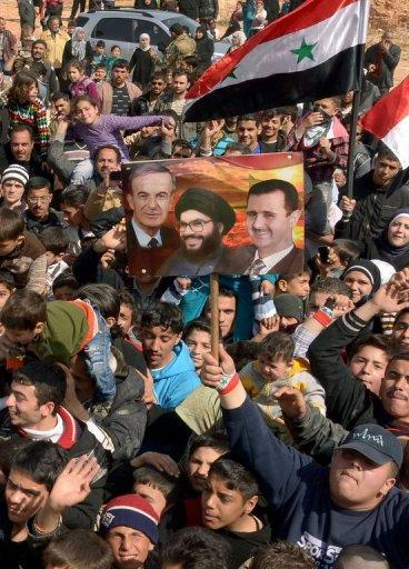 Picture released by the official Syrian Arab News Agency (SANA) on March 9, 2013, shows a man holding a poster featuring an image of Hassan Nasrallah (C) the head of Lebanon's Shiite Muslim group, Hezbollah, Syria's President Bashar al-Assad (R) and his father and former president Hafez al-Assad during a demonstration in support of the Syrian national in Hamdania, a neighbourhood of Aleppo