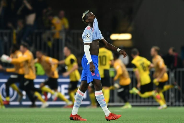 Paul Pogba walks away as Young Boys celebrate their late winner against Manchester United in Bern (AFP/Fabrice COFFRINI)