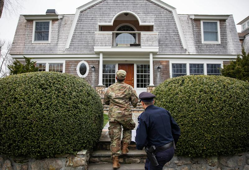 Rhode Island Air National Guard Tsgt. William Randall, left, and Westerly police officer Howard Mills approach a home while looking for New York license plates in driveways to inform them of self quarantine orders, Saturday, March 28, 2020, in Westerly, R.I.