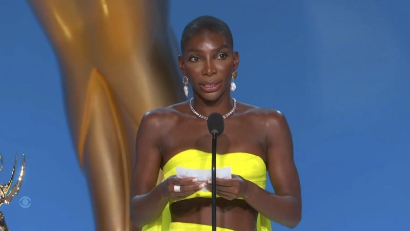 A woman in a bright yellow dress holding a piece of paper and speaking into a microphone