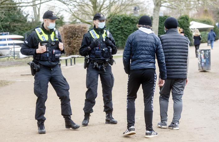 Police officers address walkers around Hamburg's Outer Alster who do not adhere to the strict mask requirement in Hamburg, Germany, Sunday, Feb.28, 2021. In case of repetition, they can impose a fine. (Markus Scholz/dpa via AP)