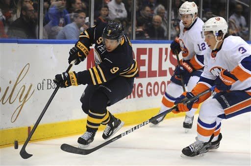 Buffalo Sabres forward Derek Roy (9) moves the puck as he is shadowed by New York Islanders forward Josh Bailey (12) and defenseman Travis Hamonic (3) in the first period of their NHL hockey game, Saturday, Jan. 14, 2012, in Uniondale, N.Y. (AP Photo/John Dunn)