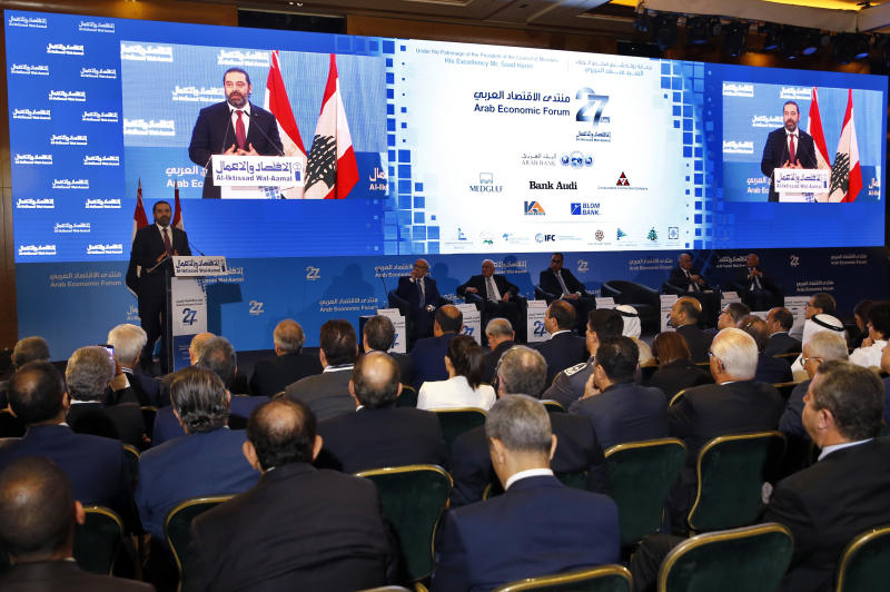 Lebanese Prime Minister Saad Hariri, left, speaks during the opening session of the Arab Economic Forum in Beirut, Lebanon, Thursday, May 2, 2019. The forum is taking place amid an economic crisis in Lebanon, which is suffering from slow growth, a high budget deficit and massive debt. (AP Photo/Bilal Hussein)