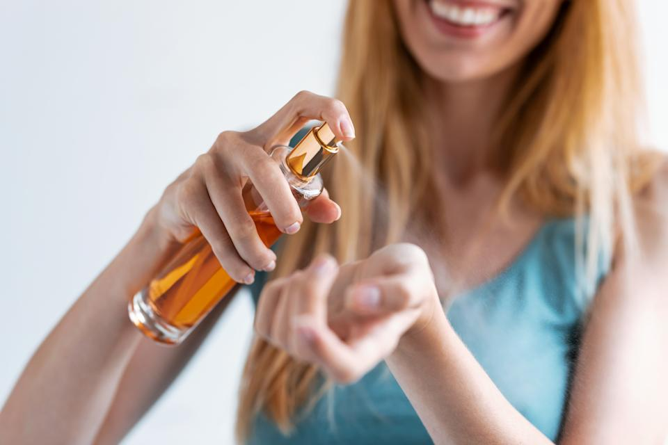 Close-up of smiling young woman applying perfume on her wrist while standing at home.