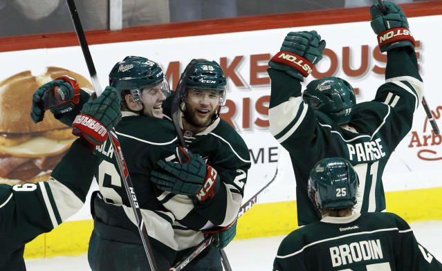 Minnesota Wild left wing Erik Haula, left, of Finland; right wing Jason Pominville, center; and left wing Zach Parise (11) celebrate Pominville's empty-net goal during the third period of Game 6 of an NHL hockey first-round playoff series against the Colorado Avalanche in St. Paul, Minn., Monday, April 28, 2014. The Wild won 5-2. (AP Photo/Ann Heisenfelt)