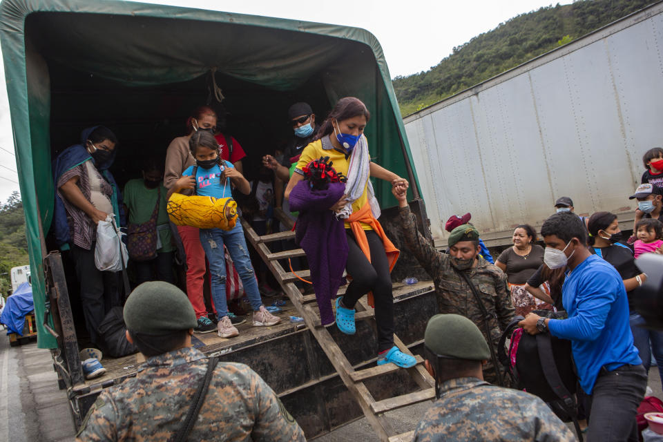 A Honduran migrant woman is helped off a Guatemalan army truck after being returned to El Florido, Guatemala, one of the border points between Guatemala and Honduras, Tuesday, Jan. 19, 2021. A once large caravan of Honduran migrants that pushed its way into Guatemala last week had dissipated by Tuesday in the face of Guatemalan security forces. (AP Photo/Oliver de Ros)