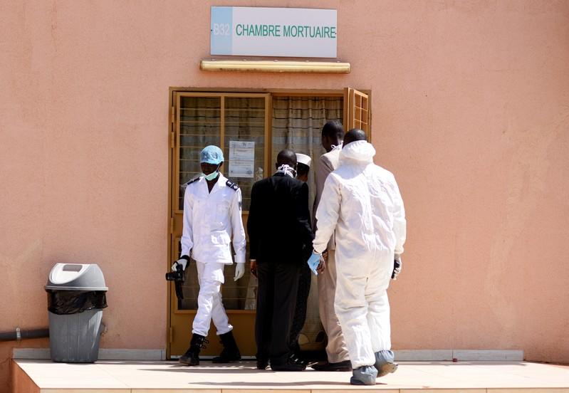 Forensic experts and medics are pictured at the door of the morgue of the Bogodogo District Hospital in Ouagadougou