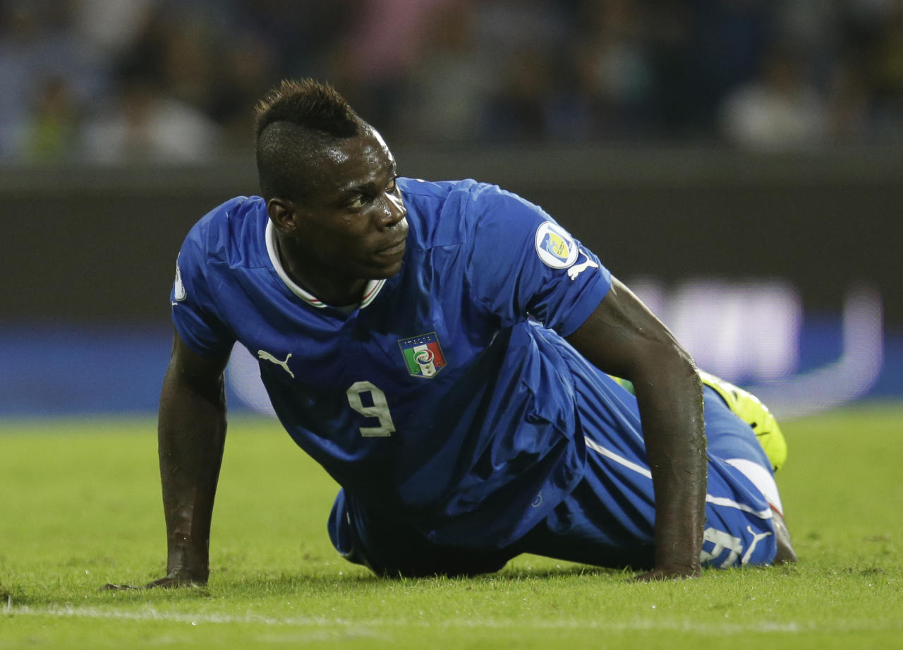 FILE - In this Oct. 15, 2013, file photo, Italy's Mario Balotelli lies on the pitch during a 2014 FIFA World Cup, Group B, qualification match between Italy and Armenia in Naples, Italy. Italy's intentions will likely depend on the wavering ways of talented forward Mario Balotelli, whose mood swings often get him into trouble both on and off the field. (AP Photo/Gregorio Borgia, File)