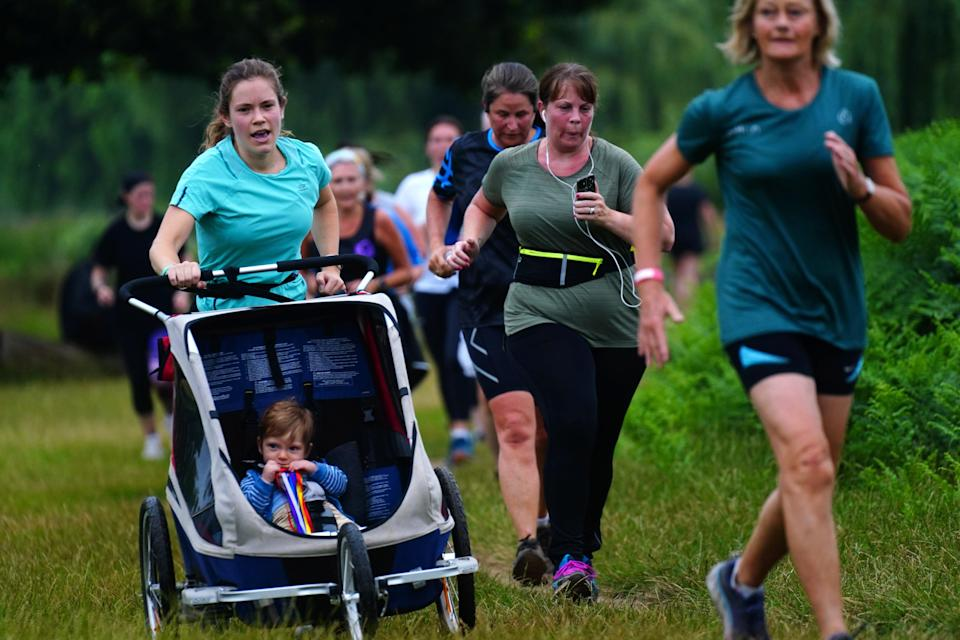 A runner pushes her buggy during Parkrun (Victoria Jones/PA) (PA Wire)