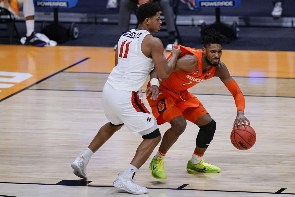 Syracuse forward Quincy Guerrier (1) goes around San Diego State forward Matt Mitchell (11) during the first half of a college basketball game in the first round of the NCAA tournament at Hinkle Fieldhouse in Indianapolis, Friday, March 19, 2021. (AP Photo/AJ Mast)
