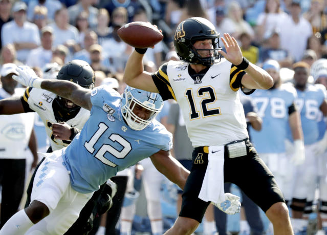 North Carolina's Tomon Fox, left, pressures Appalachian State's Zac Thomas, right, during the first quarter of an NCAA college football game in Chapel Hill, N.C., Saturday, Sept. 21, 2019. (AP Photo/Chris Seward)