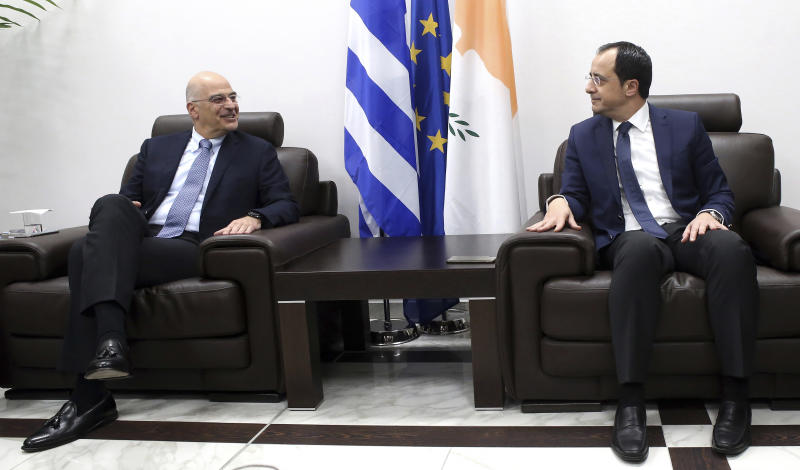 Greece's Foreign Minister Nikos Dendias, left, talks with Cypriot counterpart Nikos Christodoulides at Cyprus' main airport in the coastal town of Larnaca on Sunday, December 22, 2019. Dendias stopped off in Cyprus following a visit to Libya for contacts with Libyan National Army leader, General Khalifa Haftar and later in Egypt for a meeting with Foreign Minister Sameh Shoukry. Top of the agenda during Dendias' contacts was a maritime border deal that Turkey signed with Libya's U.N.-recognized government that Greece, Cyprus and Egypt have denounced as contrary to international law.(AP Photo/Philippos Christou)