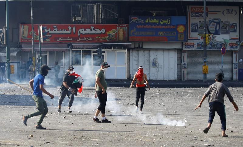 Demonstrators run as a tear gas was thrown by Iraqi security forces during the ongoing anti-government protests in Baghdad