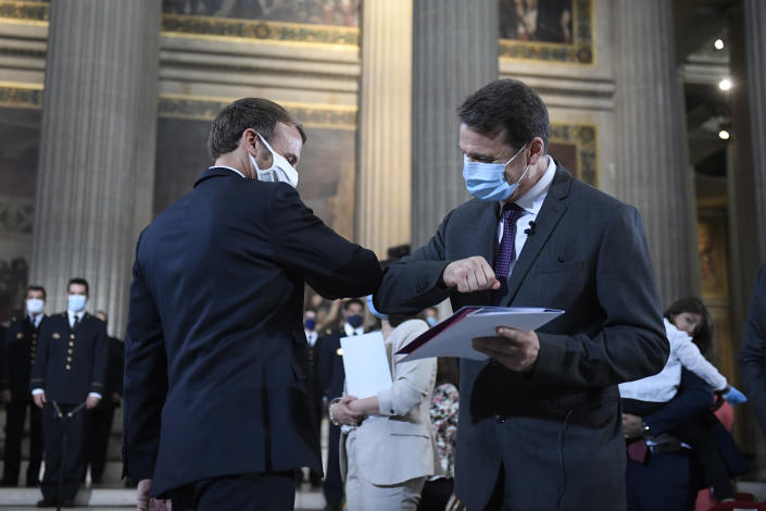 French President Emmanuel Macron, left, congratulates an unidentified new French citizen after he was granted with French Citizenship during a ceremony to celebrate the 150th anniversary of the proclamation of the Republic, at the Pantheon monument, in Paris, Friday Sept.4. 2020. (Julien de Rosa, Pool via AP)