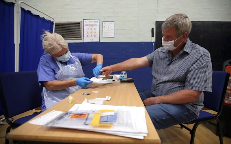 A man has his finger pricked during a clinical trial of tests for the coronavirus disease (COVID-19) antibodies, at Keele University, in Keele - Carl Recine/Reuters