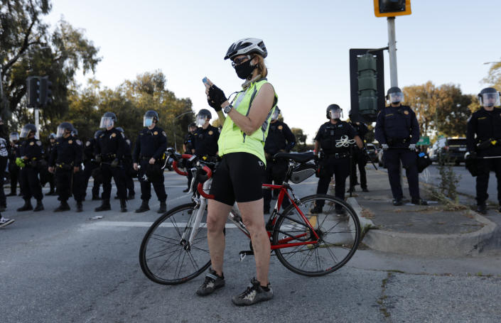 A bicyclist checks her cellphone in front of California Highway Patrol officers during a protest of the killing of George Floyd near the entrance of Highway 101 at Broadway and Woodside Road in Redwood City, Calif., on Tuesday, June 2, 2020. (Nhat V. Meyer/Digital First Media/The Mercury News via Getty Images)