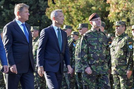 NATO Secretary-General Jens Stoltenberg and Romanian President Klaus Iohannis review NATO multinational brigade in Craiova, Romania, October 9, 2017. Inquam Photos/Bogdan Danescu/via REUTERS